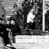 Giovani assistono alle proteste dall'alto davanti la porta di Damasco. Dietro un poliziotto israeliano tiene sotto controllo la situazione.