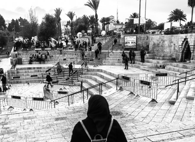 Una signora guarda il piazzale transennato davanti  la porta di Damasco. Essendo venerdì, il giorno di preghiera, tale soluzione è resa necessaria per ridurre i disordini.