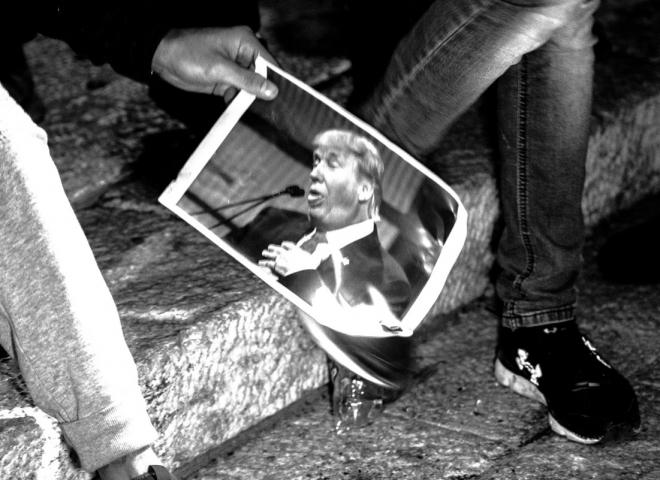 Un manifestante brucia una foto di Trump