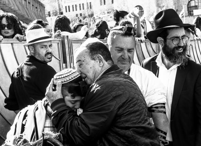 Un giovane ragazzo israeliano durante i festeggiamenti del Bar Mitzvah viene abbracciato dal padre