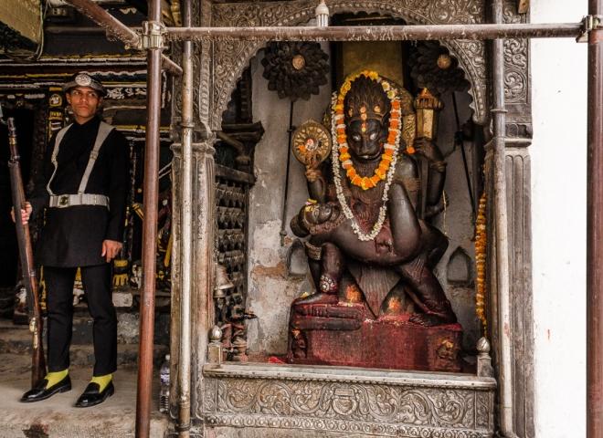 Kathmandu – Palazzo Reale: Una guardia accanto a una statua all'ingresso del palazzo. I sostegni sono ancora evidenti