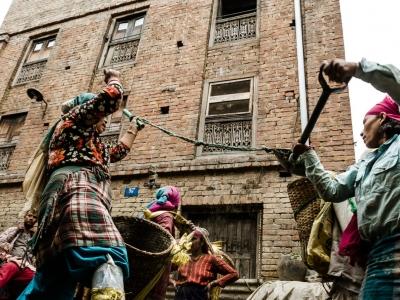 Thimi: Donne impegnate nella ricostruzione. La corda legata alla pala serve per alleggerire il lavoro