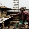 Bhaktapur: Una signora anziana passa dei mattoni durante la ricostruzione di una casa